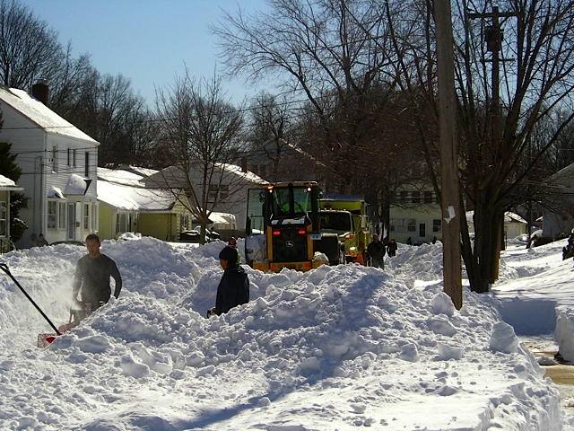 Department of Public Works crew uses heavy equipment  to free a plow truck on Brighton Street at  mid day on Sunday