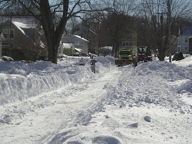 The path is cleared for plow to make its pass on Brighton Street -- a scene going on throughout the city on Sunday afternoon.