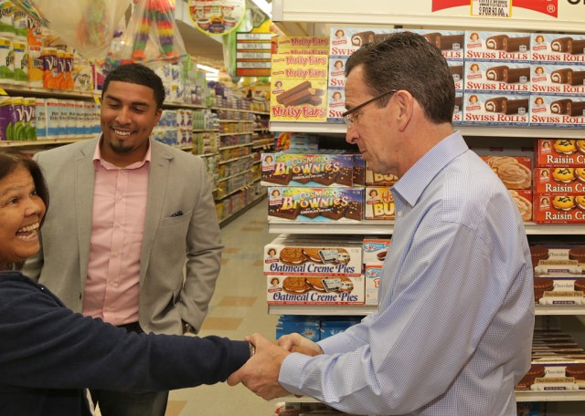 Governor Malloy greets shopper on Election Day in downtown New Britain. Ward 3 Ald. Manny Sanchez (center) looks on (F. Gerratana photo)