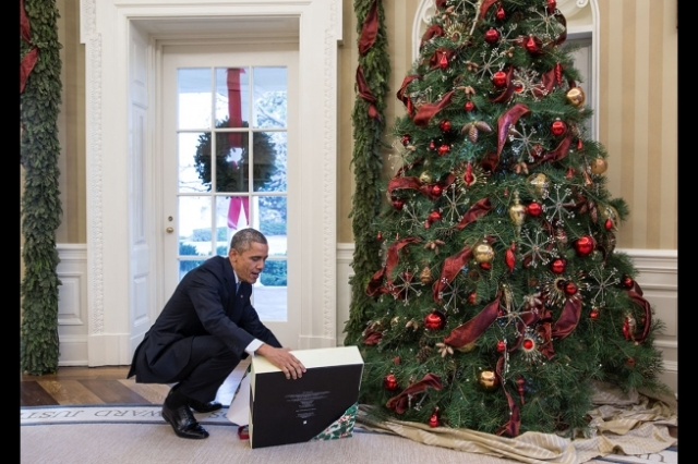 President Barack Obama opens a Christmas gift from Personal Secretary Ferial Govashiri in the Oval Office, Dec. 19, 2014. (Official White House Photo by Pete Souza)